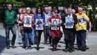 Families of those who died in the Ballymurphy Massacre hold images of the deceased outside Laganside Court in Belfast. Photograph:  Niall Carson/PA Wire.