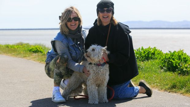 Sarah Shannon (left) and Margo Shannon from Clonskeagh with Millie, a cockapoo, enjoying the good weather at Dollymount Beach, Dublin. Photograph: Collins