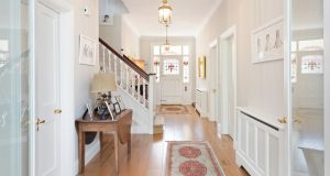 The front door, one of the few on the road not screened by a porch, yields to a broad wide-plank oak floor hall