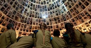 Israeli soldiers stand under pictures of Jews killed in the Holocaust during a visit to the Hall of Names at Yad Vashem's Holocaust History Museum in Jerusalem. Photograph: Baz Ratner/Reuters