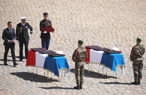 Late special forces soldiers Cedric de Pierrepont and Alain Bertoncello, killed in a raid to free hostages in Burkina Faso last week, are posthumously awarded with the medal of Commander in the Legion of Honor by French president Emmanuel Macron as he stands before their flag-drapped coffins. Photograph: Christophe Petit Tesson/AFP/Getty