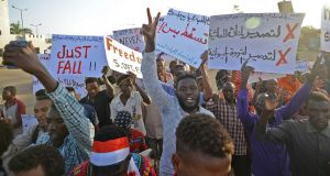 Sudanese protesters  wave placards during a demonstration in Khartoum on Tuesday. At least four people were killed on Monday in new clashes between protesters and  security forces. Photograph: Mohamed El-Shahed/AFP/Getty Images
