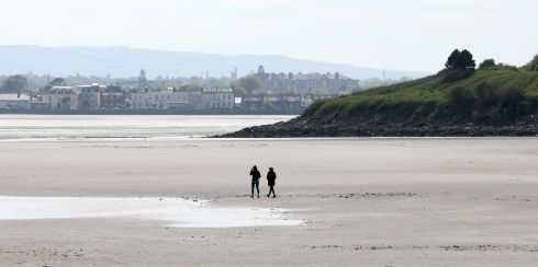 PEACE AND QUIET: People walk on the beach from the South Bank Road towards Sandymount in Dublin. Photograph: Laura Hutton