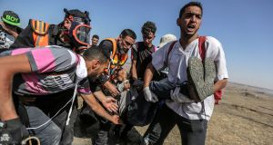 Palestinians carry a wounded youth during the clashes that occurred today near the border between Israel and the eastern Gaza Strip. Photograph: EPA