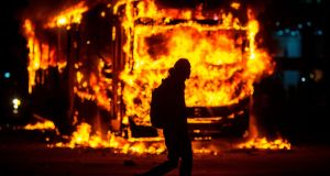 "A bus in flames at a protest organised by the National Students Union in Rio de Janeiro: Students and teachers began a nationwide demonstration on Wednesday in ""defence of education"". Photograph: Mauro Pimentel/AFP"