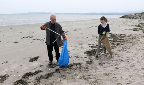 CLEANING UP: Writers gather for a beach clean-up inspired by 12-year-old Flossie Donnelly (right) on Poolbeg beach in Ringsend, Dublin. Among those taking part were John Banville (left). Photograph Nick Bradshaw/The Irish Times