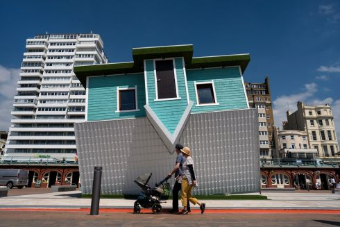 TOPSY-TURVY: Members of the public pass a new art installation called 'Upside Down House' on the promenade at the seafront, in Brighton, UK. The installation will open to the public on May 18th and will be available to visit for 12 months. Photograph: Will Oliver/EPA