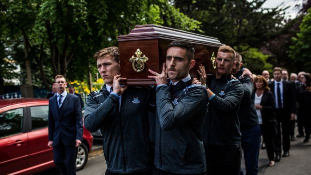 Brian Howard, Niall Scully and Ciarán Kilkenny (right, behind) of the Dublin senior football team carry the coffin of Anton O'Toole into the Mount Argus church in Kimmage. Photograph: James Forde