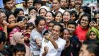 Joko Widodo takes a selfie with local residents after his victory speech following the announcement of election results at a slum area in Jakarta, Indonesia, on Tuesday. Photograph: Mast Irham/EPA