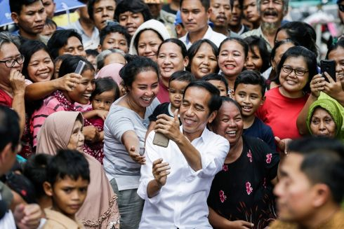 POPULARITY CONTEST: Indonesia's Incumbent President and member of the Indonesian Democratic Party of Struggle, Joko Widodo, takes a selfie with locals after his victory speech following the election results IN a slum area in Jakarta, Indonesia. Photograph: Mast Irham/EPA