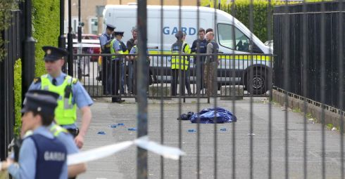 SAD TALLY: The body of a man lies covered with a blanket at the scene of a fatal gun attack at the grounds of the Church of Our Lady Immaculate, Darndale, Dublin, on Wednesday evening. Another man had been shot dead in Dublin the previous evening. Photograph: Colin Keegan/Collins Dublin