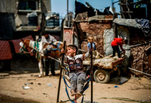 SUNNING HIMSELF: A Palestinian boy rides on a makeshift swing in Beit Lahia, in the northern Gaza Strip. Photograph: Mohammed Abed/AFP/Getty