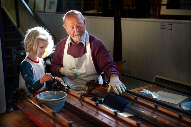 Freya Leathley Barthel (6) from Raheny, with Don Kerrigan from Churchtown, using a pen ruling machine in the National Print Museum. Photograph: Dara Mac Dónaill/The Irish Times