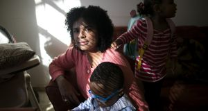 Saffiatu Sillah, whose circumcision caused her  agonising pain during the births of her children, Mijan  and Jaria, at home in Philadelphia. Photograph: Maddie McGarvey/ The New York Times