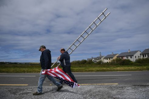 DONALD AT DOONBEG: Tommy Haugh and Danny Buckley carry a ladder and a US flag to festoon the streets of Doonbeg village ahead of a visit by US president Donald Trump to his golf course in the Co Clare village. Photograph: Clodagh Kilcoyne/Reuters