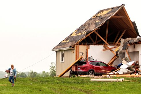 GIMME SHELTER: A woman walks away from a damaged house after tornadoes strike in Linwood, Kansas. Photograph: Nate Chute/Reuters