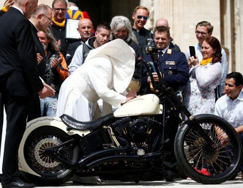 "JESUS BIKER: Pope Francis signs a Harley Davidson motorbike of the Christian motorcycle group ""Jesus Biker"" during the weekly general audience at the Vatican. Photograph: Yara Nardi/Reuters"