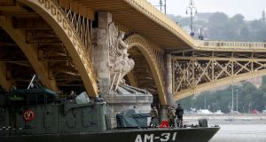 A Hungarian army boat passes under Margit Bridge after several people were killed in an accident on the Danube river in Budapest. Photograph:  Bernadett Szabo/Reuters