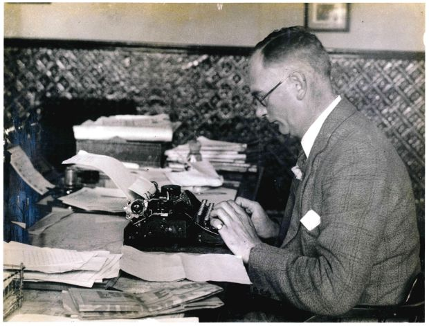 "Journalist Tom ""Cork"" Kenny working at a typewriter"