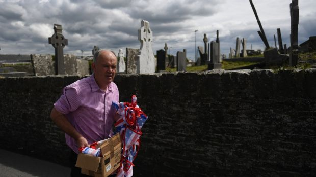 Publican Tommy Tubridy helps to put up stars and stripes bunting to festoon the streets of Doonbeg village with US colors sooner than a plod to by US President Donald Trump to his golf route within the County Clare village of Doonbeg, Ireland. Photo: Clodagh Kilcoyne/Reuters