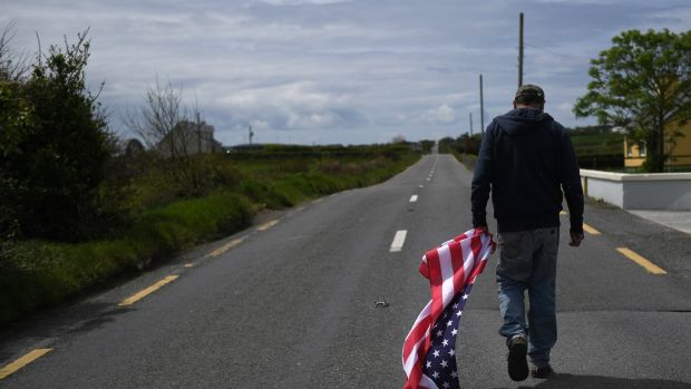 Tommy Haugh carries a US flag to festoon the streets of Doonbeg village sooner than a plod to by US President Donald Trump to his golf route within the County Clare village of Doonbeg, Ireland. Photo: Clodagh Kilcoyne/Reuters