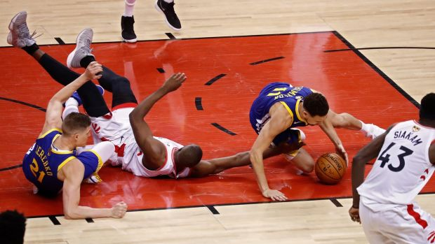 Toronto Raptors player Serge Ibaka goes for a loose ball against Golden State Warriors players Jonas Jerebko and Klay Thompson during the second half of the NBA Finals game one at Scotiabank Arena in Toronto, Canada. Photo: Larry W Smith/EPA