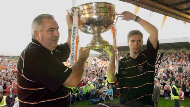 Armagh manager Joe Kernan and captain Kieran McGeeney hold the Sam Maguire cup aloft in front of Armagh fans on the team's homecoming in Crossmaglen in 2002. File photograph: Brendan Moran/ SportsfIle