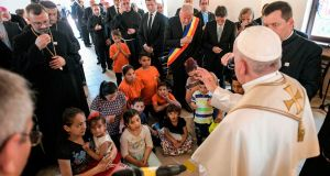 Pope Francis blessing children during a meeting with members of the Roma community in Blaj, Romania. Photograph: Vatican Media handout/AFP/Getty