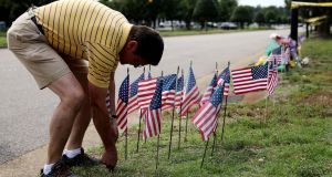 Rich Lindgren places 12 US flags in the ground at a makeshift memorial outside  the  scene of a mass shooting at the Virginia Beach Municipal Center,   Virginia Beach, Virginia. Photograph: Chip Somodevilla/Getty