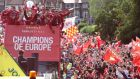 Liverpool's players with the Champions League trophy on board a parade bus   in Liverpool, England. Photograph:  Nigel Roddis/Getty Images