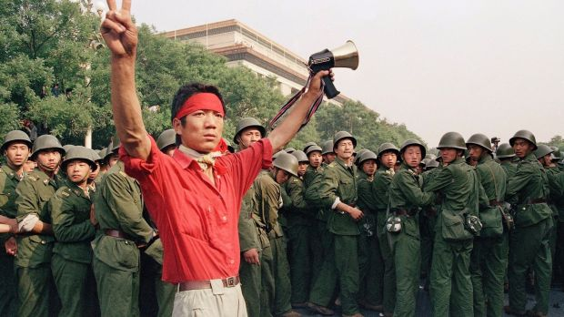 A student pro-democracy protester flashes victory signs to the crowd on Saturday, June 3rd, 1989, as People's Liberation Army troops withdraw. Photograph: Mark Avery