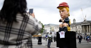 A demonstrator takes a picture of  Donald Trump statue, during a protest in Trafalgar Square, London. Photograph: Clodagh Kilcoyne/Reuters