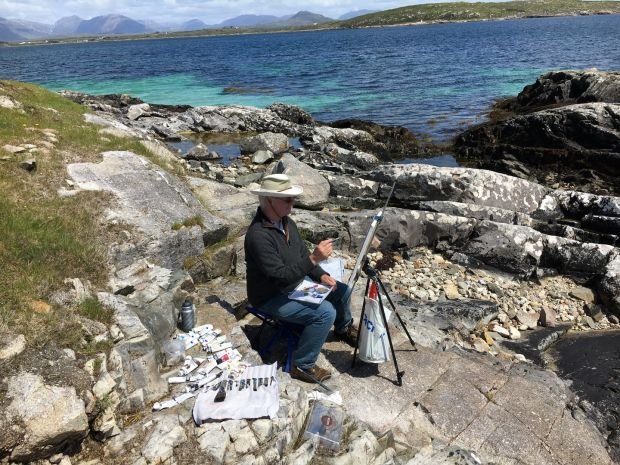 Michael Doherty working in windy conditions by the shore, easel weighted down with a bag of stones, 2018. Photograph: Nancy Keefe Rhodes