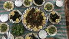 Mansaf surrounded by various salads in the home of Um Haya and Abu Haya in Azraq camp