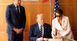 US first lady Melania Trump  signs the visitors book at Shannon Airport as Taoiseach Leo Varadkar and US president Donald Trump  watch on. Photograph: Pool/Getty Images.