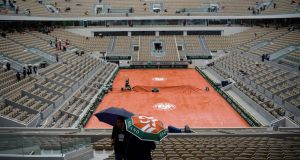 People hold their umbrella in the empty stands as rain falls on Wednesday at the Roland Garros 2019 French Open. Photo: Christophe Archambault/Getty Images