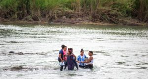 A group of Central American migrants attempt to cross the Rio Grande in Eagle Pass, Texas. Photograph: Ilana Panich-Linsman/The New York Times