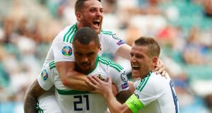 Northern Ireland's Josh Magennis celebrates scoring their second goal with team-mates Conor Washington  and Steven Davis. Photograph: Ints Kalnins/Reuters