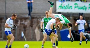 Fermanagh's Ryan Jones takes a tumble as he's challenged by Monaghan's Kieran Hughes. Photograph: Tommy Dickson/Inpho