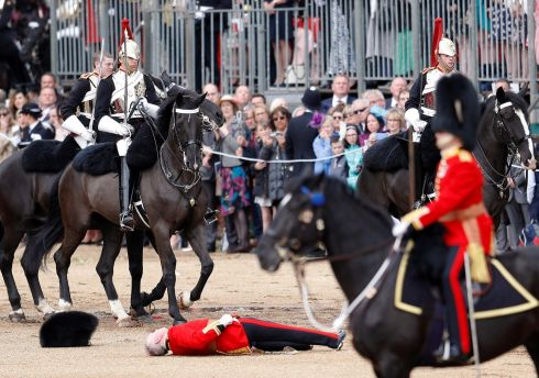 FLAT OUT: A guardsman on the ground after falling off his horse during the Trooping the Colour parade in central London. Photograph: Peter Nicholls/Reuters