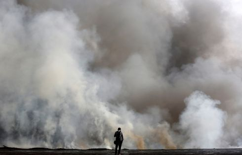 HOLDING HIS BREATH: A man watches smoke billowing from a chemical and a cloth warehouse after a fire broke out at the site, on the banks of the river Ganges in Kolkata, India. Photograph: Rupak De Chowdhuri/Reuters