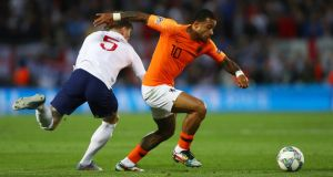 Memphis Depay of the Netherlands evades John Stones of England. Photograph: Dean Mouhtaropoulos/Getty