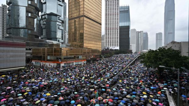 Protesters shelter under umbrellas during a downpour as they occupy roads near the government headquarters in Hong Kong. Photograph: Anthony Wallace/AFP/Getty Images
