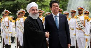 Iranian president Hassan Rouhani shakes hands with Japan's prime minister Shinzo Abe during a welcome ceremony in Tehran on Wednesday. Photograph: Handout via Reuters
