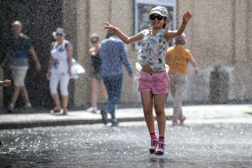 THAT'S BETTER: A girl is sprayed with water to cool down as the temperature hit 33 degrees in Prague, Czech Republic. Photograph: Martin Divisek/EPA