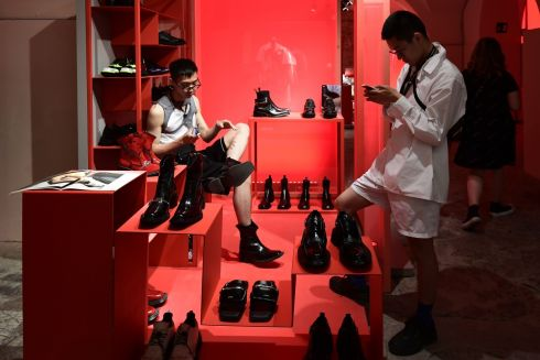 FILL YOUR BOOTS: Visitors try on shoes at the pavilion of China, the guest nation at the Pitti Immagine Uomo fashion event in Florence, Tuscany. Photograph: Miguel Medina/AFP/Getty Images