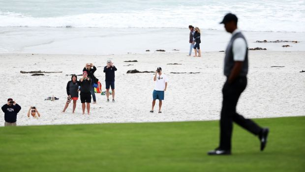 Spectators on the beach watch Tiger Woods walk down the 10th hole. Photo: Christian Petersen/Getty Images