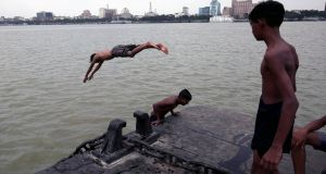 Boys jump into the Ganges river to cool off during hot weather in Kolkata, India, on June 11th. Photograph:   Piyal Adhikary/EPA
