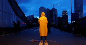 MEMORIAL PROTEST: A protester against the controversial extradition Bill in Hong Kong wears a yellow raincoat to pay tribute to another protester who died after falling from scaffolding at the Pacific Place complex. Photograph: Tyrone Siu/Reuters