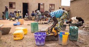 A girl washes clothes as families stand outside a school used as a shelter for Internally Displaced People from northern Burkina Faso in Ouagadougou. Photograph: Olympia De Maismont/AFP